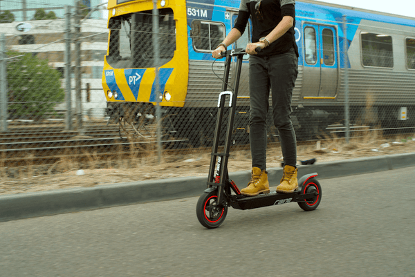 Electric scooter being ridden next to a train