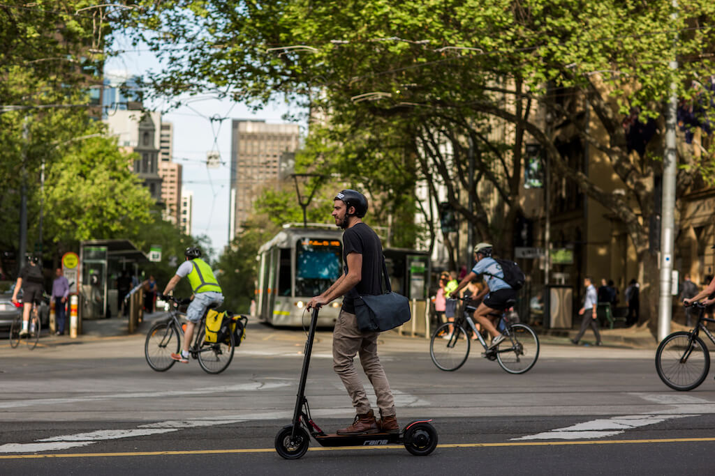 Man riding an electric scooter through a city wearing a helmet