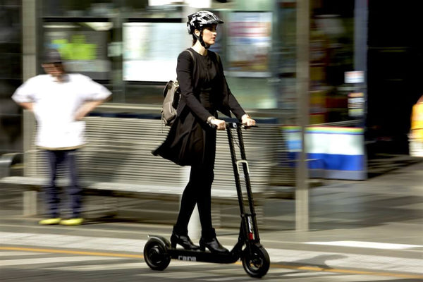 Woman riding electric scooter through city wearing a helmet