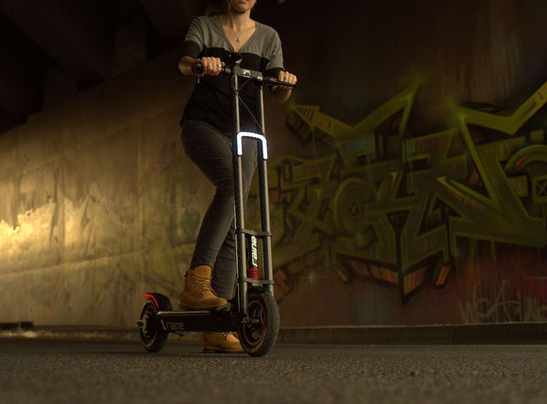 Person riding electric scooter at night