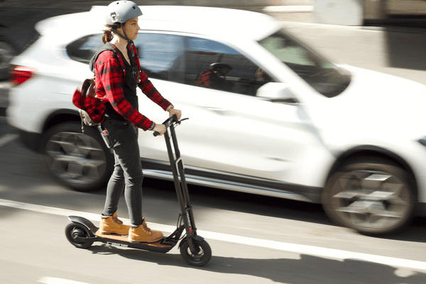 Woman riding electric scooter with helmet