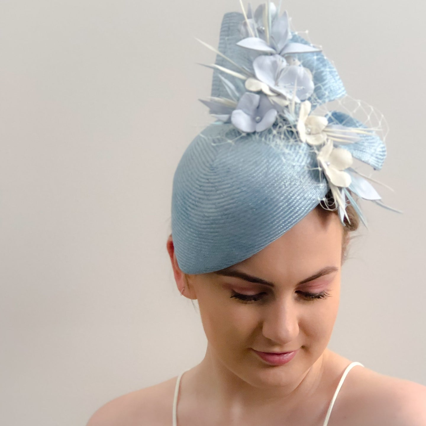 LIGHT BLUE AND CREAM SIDE SITTING RACE HAT WITH LEATHER FLORAL FEATURE