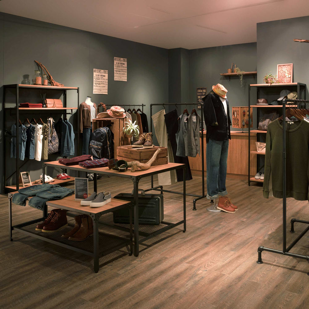rustic industrial shop interior with gas-pipe clothes racks by Store Express