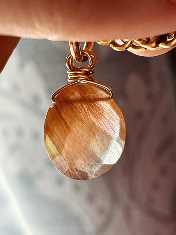 Golden rutilated quartz necklace with gold chain held by hand