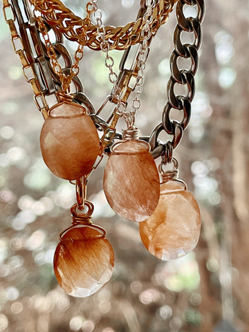 collection of golden rutilated quartz necklaces held baby hand against natural background