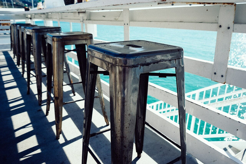 metal bar stools outside by the water