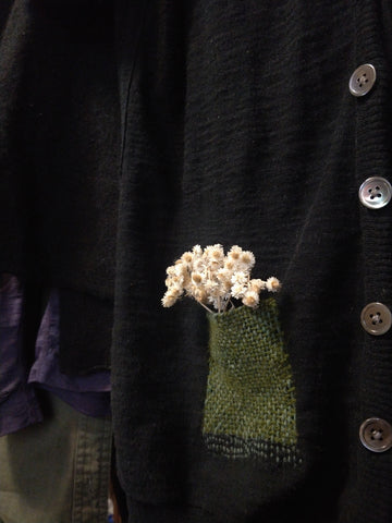 Black cardigan with green patch pocket. White flowers have been placed in the pocket as embellishment.