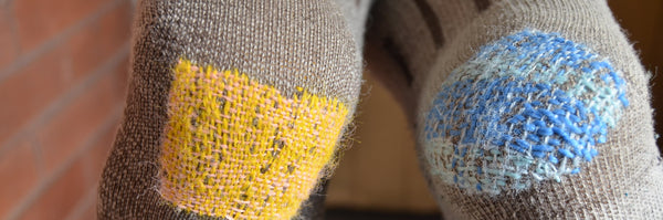 A pair of wool socks with heels colourfully patched in pink/yellow (left) and blue (right)