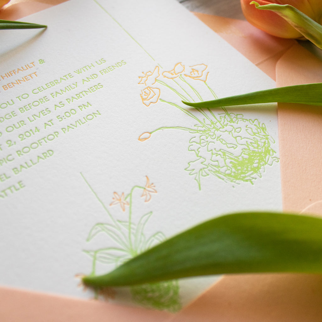 detail of letterpress kokedama floral design wedding invitations in spring green and peachy-orange inks