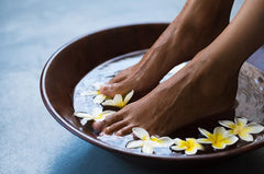 Feet soaking in bowl of water and flowers