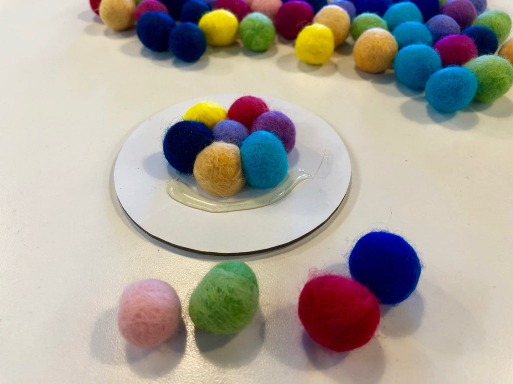 6 Wool Pom Poms glued to canvas circle
