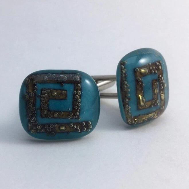 A pair of light-blue fused-glass cufflinks with brass spirals.