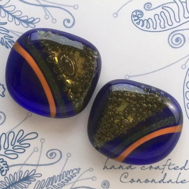 A pair of blue fused-glass cufflinks with orange stripes and brass triangles.