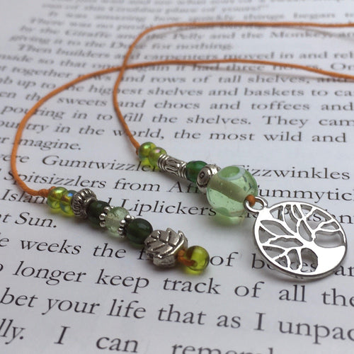 A beaded string bookmark with a silver tree-of-life charm.