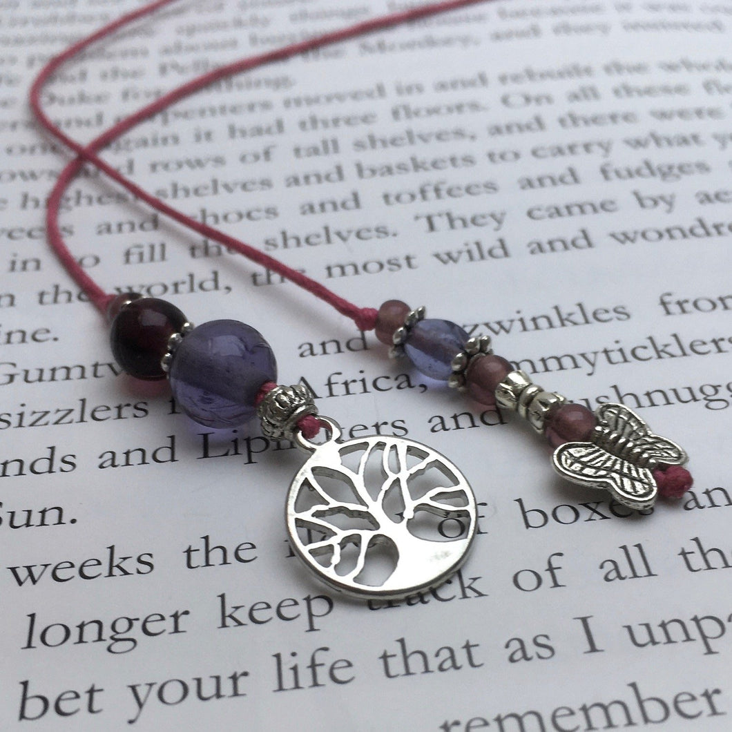 A beaded string bookmark with a silver butterfly and tree-of-life charm.