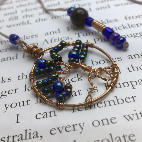 A copper wire tree of life bookmark with iridescent blue beads laying on an open page.