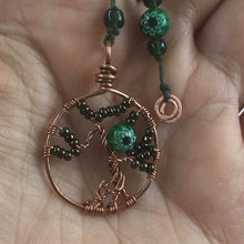 Load image into Gallery viewer, A copper wire tree of life bookmark with green beads laying on an open hand.