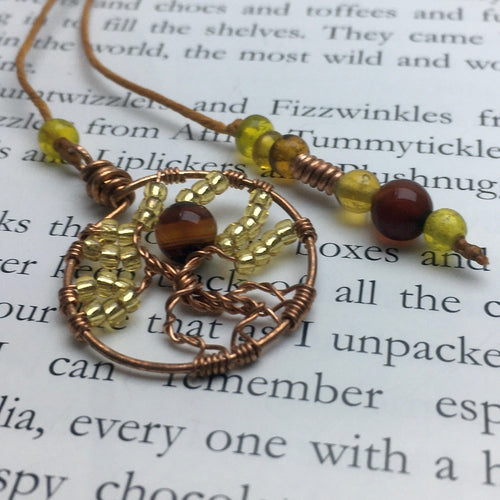 A copper wire tree of life bookmark with yellow and brown beads laying on an open page.