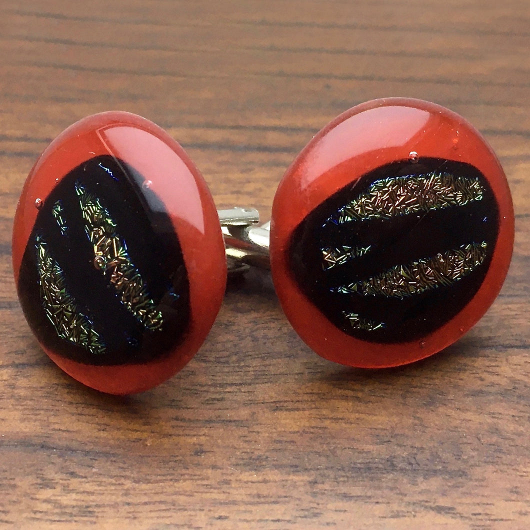 A pair of red fused-glass cufflinks with dichroic features.