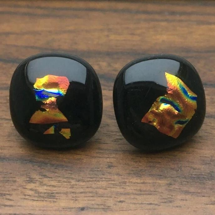A pair of black fused-glass earrings with dichroic features.