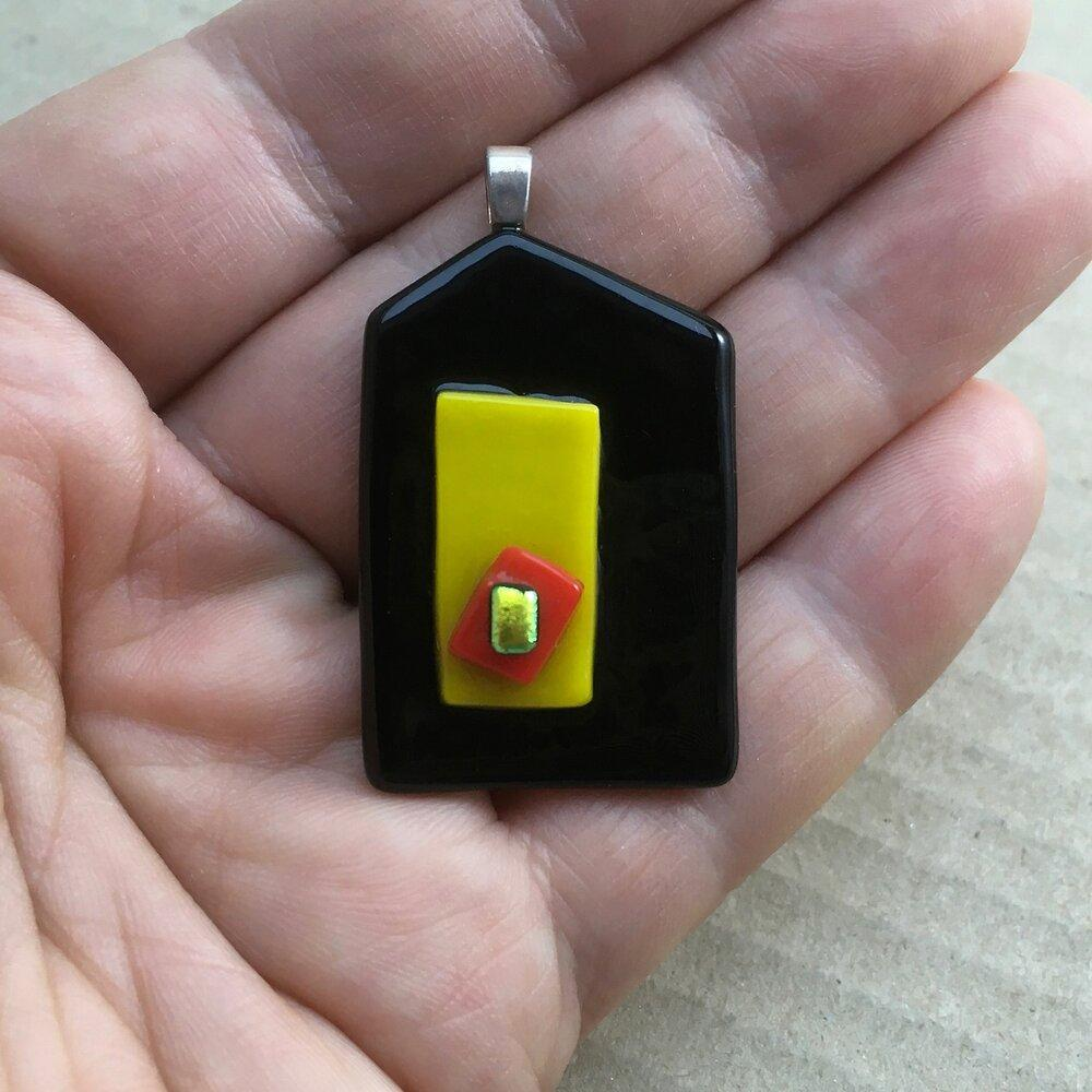 A black and yellow fused-glass pendant with a dichroic feature.