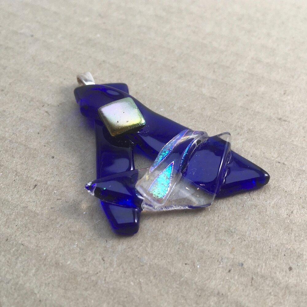 A blue and clear fused-glass pendant with dichroic features.