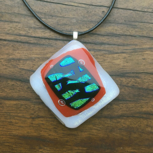 A red and white fused-glass pendant with dichroic wave features.