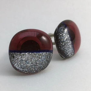 A pair of red fused-glass cufflinks with silver dichroic on half.