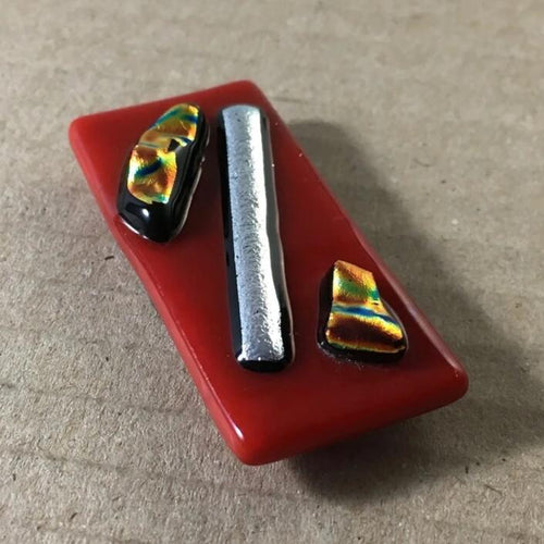 A red fused-glass magnet with silver and gold dichroic features.