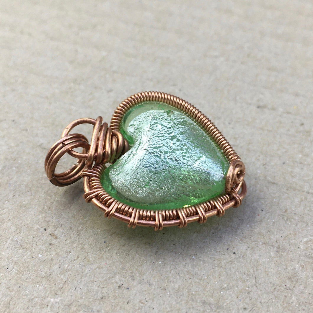 copper wire wrapped green foiled-glass bead in the shape of a heart