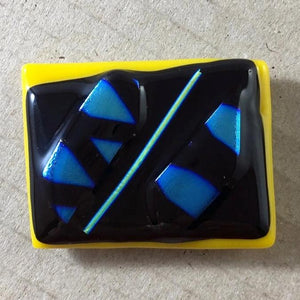 A yellow and black fused-glass magnet with blue dichroic features.
