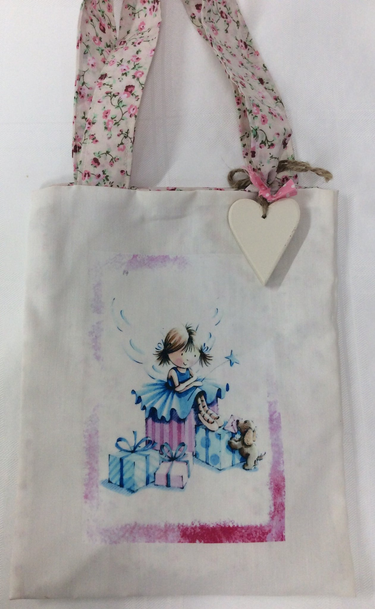 Children's handmade bag with personalised wooden heart with fairy and presents design.