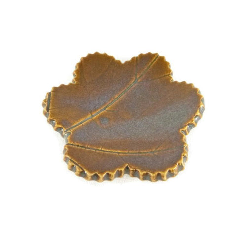 Iron Lustre trivet with leaf veining.
