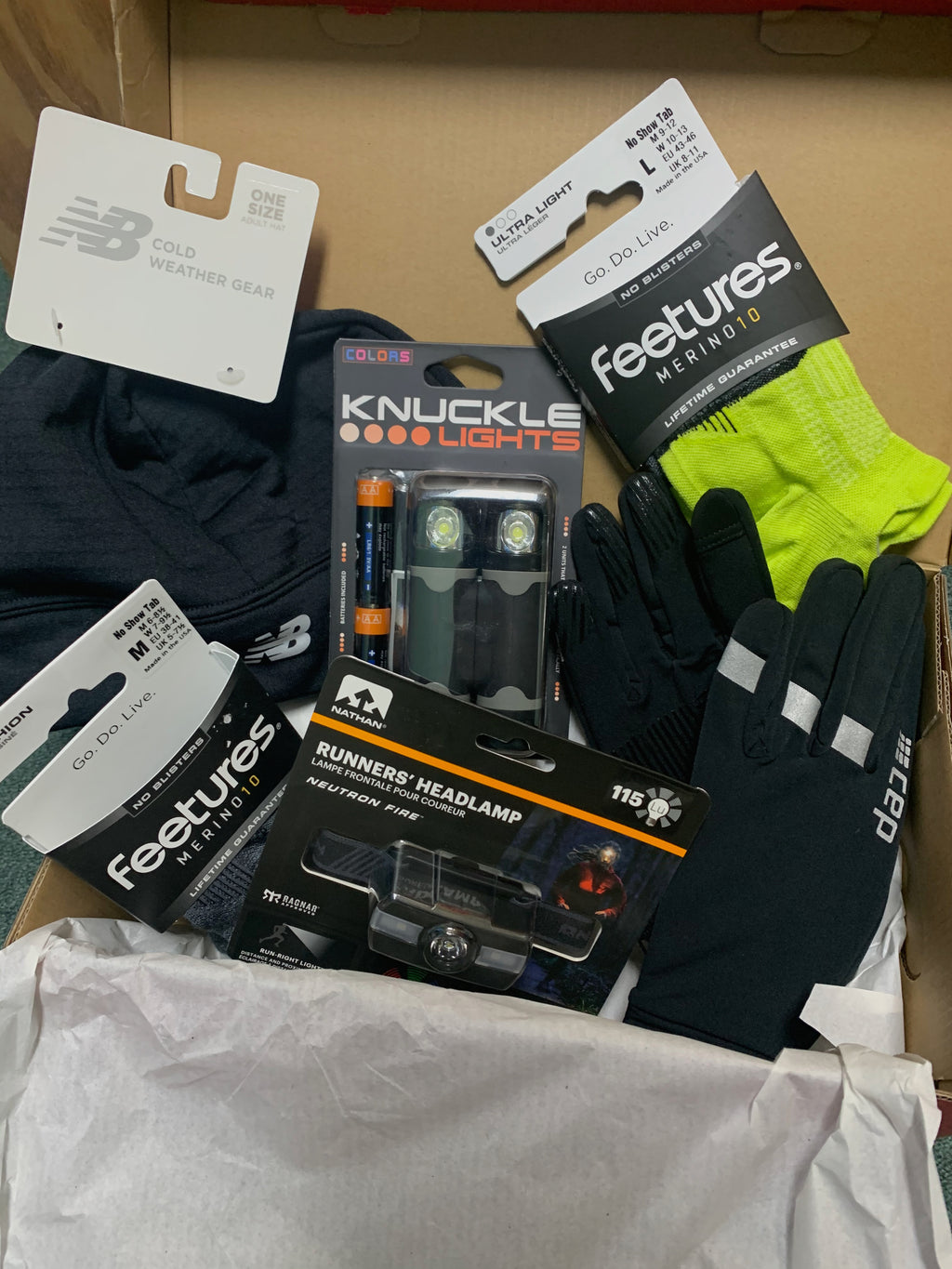 Christmas gift idea for runners this winter, this box has gloves, a hat, merino wool socks, and either a headlamp or knuckle lights. Perfect for the dark, cold winter months!