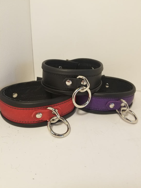 Trio of rolled deluxe collars, one black, one red and one purple.