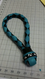A turquoise and black Braided Leather Loop Slapper.
