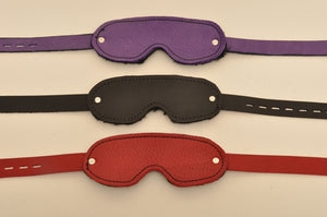 A purple, a black, and a red blindfold lying parallel to each other.