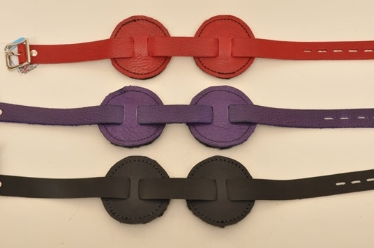 One red, one purple and one black round blindfold lying parallel to each other.