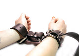 A closer shot of the Restraint Trick Belt being used as handcuffs.
