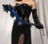 Different angle of a  woman in a black corset and skirt, holds up a blue and black Deertan Cowhide Flogger