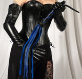 Third photo of a woman in a black corset and skirt, holding up a blue and black Deertan Cowhide Flogger.