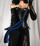 A woman in a black corset and skirt, holds up a blue and black Deertan Cowhide Flogger