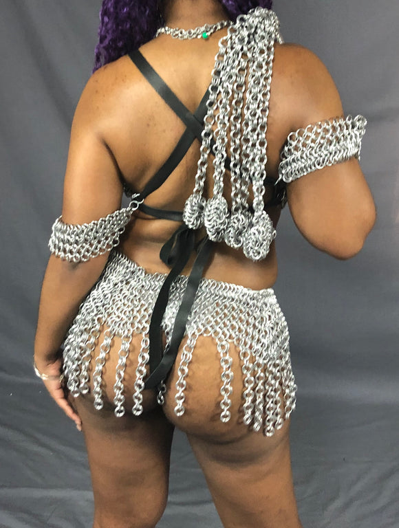 A model wearing chainmail and holding the Chainmail Ball Flogger slung over the shoulder.