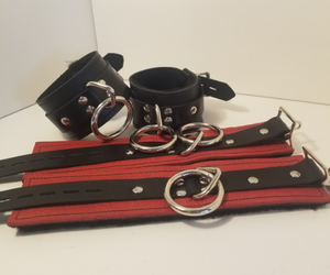 Pair of black Basic Fleece Wrist Restraint Cuffs displayed buckled, and a red pair displayed laying flat.