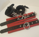 Another camera angle of a pair of black Basic Fleece Wrist Restraint Cuffs displayed buckled, and a red pair displayed laying flat.