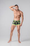 Masculine model wearing zipper rear trunks with a black base color and accented with neon green lines on the waistband, hips, upper thighs, and codpiece. Small designer logo on the front waistband.