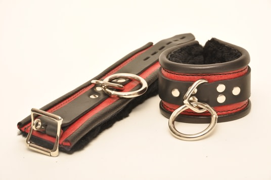 A pair of red and black Rolled Leather Fleece Deluxe Cuffs.
