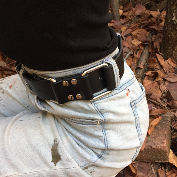 The torso of a girl in a black shirt and light blue jeans, wearing the Restraint Trick Belt on her waist.