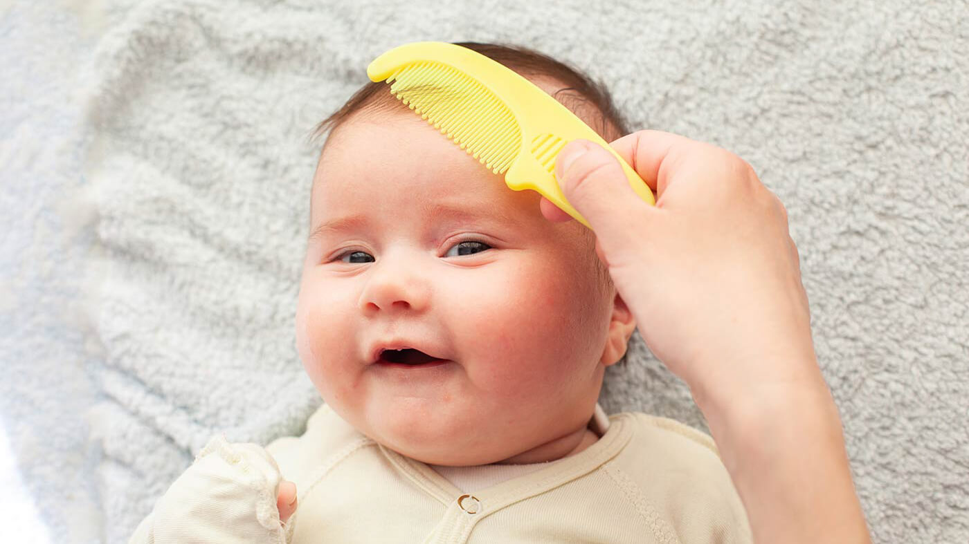 baby getting their hair combed with a yellow comb