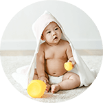 baby set playing with a hooded towel on
